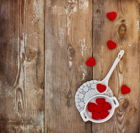 Cup, spoon and hearts on a wooden background. Concept of Valentines Day
