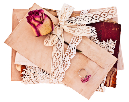 Old letters and notebook tied with lace ribbon. Isolated on white background