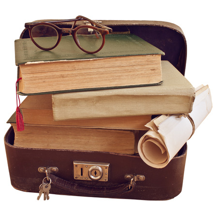 Old small suitcase with books and glasses photo
