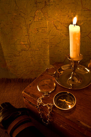 Burning candle and the compass on the old map background photo