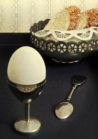 White boiled egg in silver cup and fresh baguette slices photo