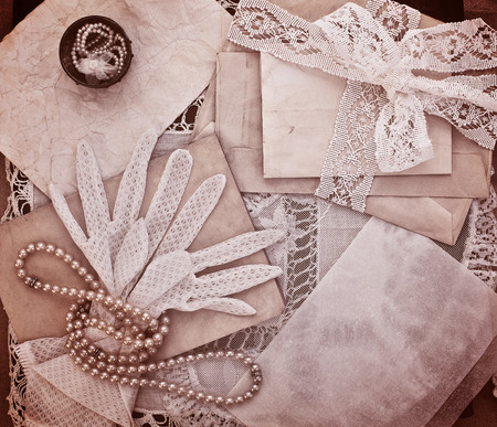 Vintage women's jewelry and gloves. Bundle of old letters with lace ribbon. Monochrome version photo