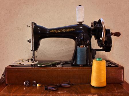 antique scissors: Old sewing machine with scissors and glasses. Sewing machine with manual transmission. Retro concept