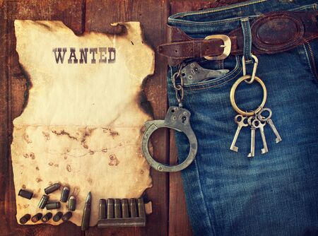 background in the style of the American West  Handcuffs in jeans pocket and tracing criminal advertisement on wooden table photo