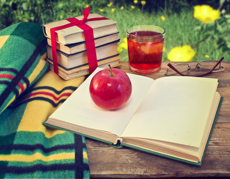 Open book on table in garden  Still life with books and apple photo