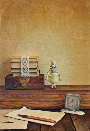 Vintage composition with books and porcelain doll. photo