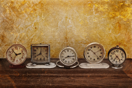 Old clock on a grungy background. Collection of vintage watches photo