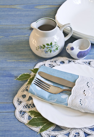 Vintage table setting with leaves decorations, napkins on a blue wooden board background Stock Photo