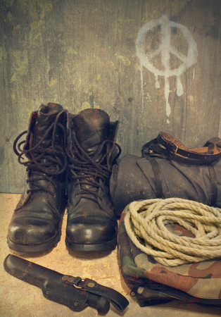 combat boots: Army boots on the background wall with a sign of pacifism Stock Photo
