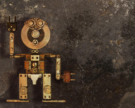 Robot of the metal parts on a dark grungy background photo
