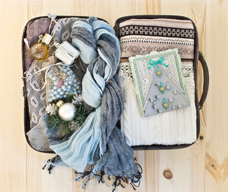 Small road suitcase with warm clothes, womens jewelry and handmade Christmas cards photo