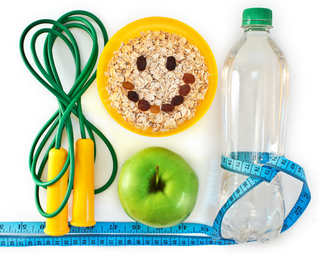 Bottle of water, muesli and green apple. Attributes of a healthy lifestyle
