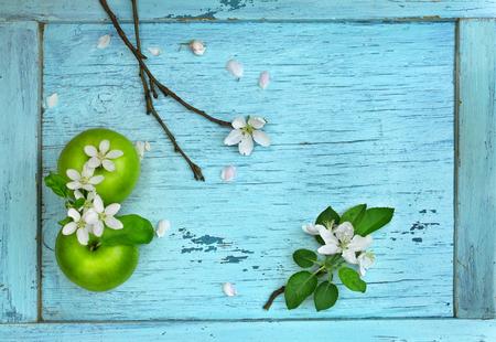 緑のリンゴと青い木製のテーブルの花