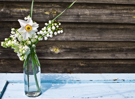 Bouquet of white spring flowers in a bottle on blue wooden table on a background of old boards photo