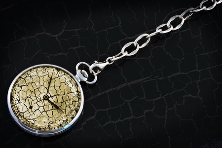 Antique pocket watch on a silver chain on the cracked black background photo