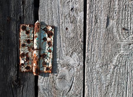crannied: Old rusty metal door hinge on wooden door
