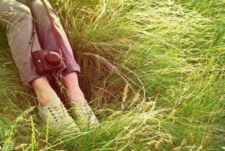 Feet woman and vintage retro photo camera outdoor. Girl sitting on the grass