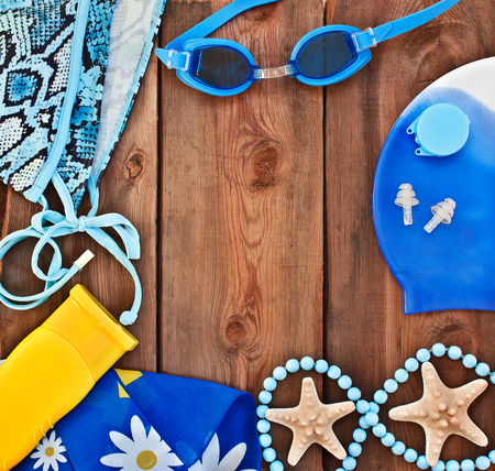 goggles, shells, swimsuit on a wooden background  set for the beach