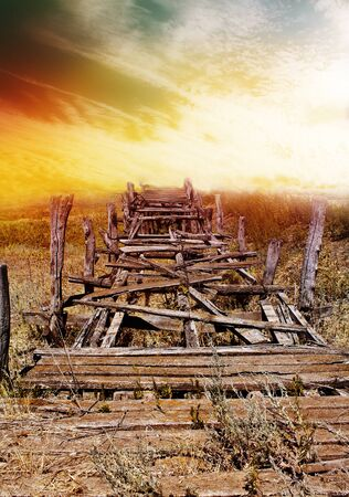 Old wooden bridge over the river in the countryside photo