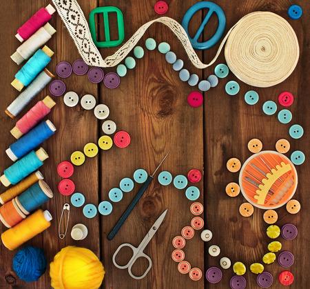 kit de costura: Hilo, botones y accesorios para la costura en el fondo sucio de madera