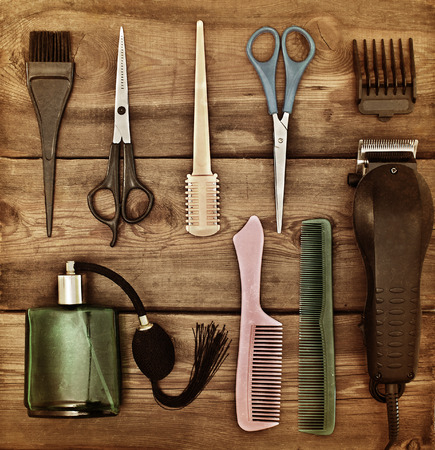 Hairdressing accessories. Retro concept. Scissors and combs on a wooden table. toning Standard-Bild