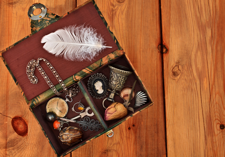 Vintage box with trinkets and womens jewelry on wooden background photo
