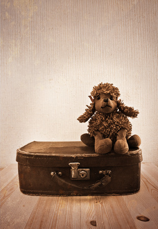 Old toy on a small road suitcase. Sepia toning. Imitation of old postcards photo