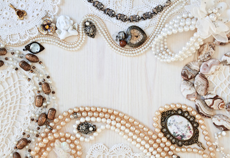 Beautiful female jewelry and trinkets on a light wooden background