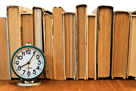 Vintage alarm clock on the background of a stack of old books on a wooden shelf Stock Photo