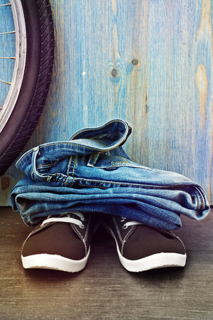 Jeans and sneakers on a background of blue wooden fence photo