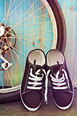 Shoes and a bicycle wheel on a background of blue wooden fence. Instagram. toning photo