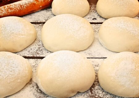 kneading: The dough on a floured wooden board. Stock Photo