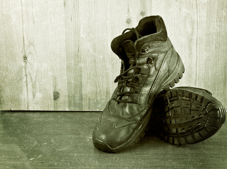 untied: Old shoes on a wooden floor.  Aged photo.