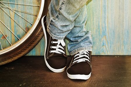 feet in jeans and sneakers alongside a bicycle photo