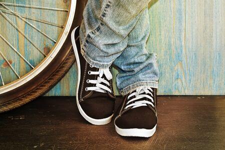 bicicleta: pies de los pantalones vaqueros y zapatillas de deporte junto a una bicicleta