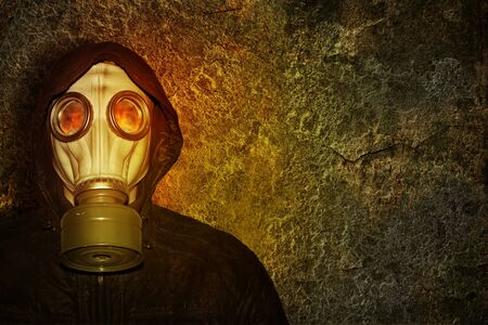 A man in a gas mask in the light of the flame flames on a concrete wall background photo