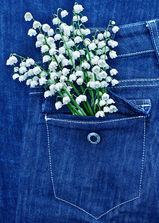 Bouquet of lily of the valley in the pocket of jeans