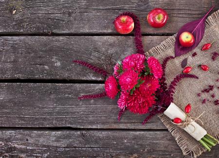 秋のブーケ。アスター、アマランサス、古い木製テーブルの上のリンゴ
