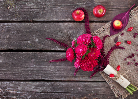 Autumn Bouquet. Asters, amaranth and apples on an old wooden table Standard-Bild