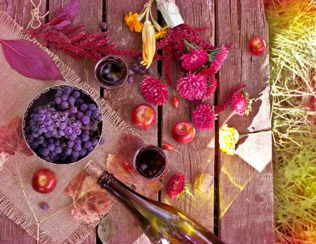 リンゴ、アスター、秋は紅葉、古いテーブルの上にワインのボトル。ワインと秋の庭にブドウの木のテーブル。