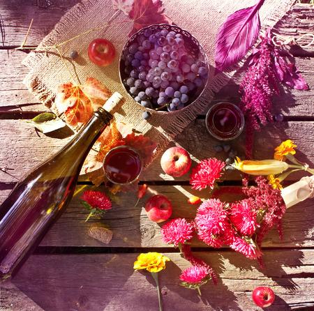 ワイン、ブドウ、汚れた木製のテーブルの上の花。秋の組成物。秋の庭でピクニック。平面図です。調子を整える