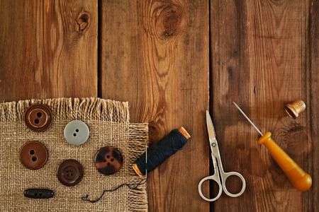 kit de costura: accesorios de costura: tijeras, dedal, hilo, botones, punzón sobre una mesa de madera