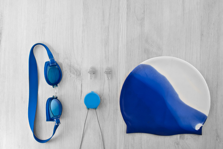Accessories for swimming in the pool on a gray wooden background