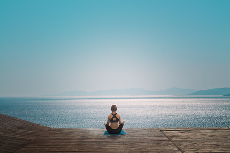 Young woman practices yoga on the beach. Meditation. Sea horizon. Stok Fotoğraf