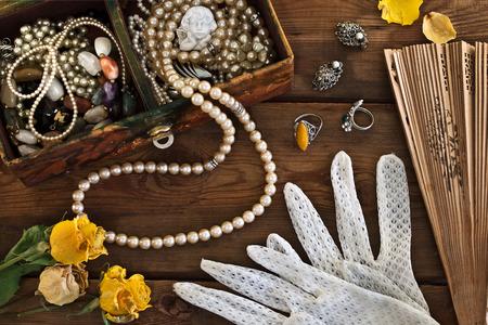 mujer con rosas: Rectángulo de la vendimia con las baratijas y joyas en el fondo de madera Foto de archivo
