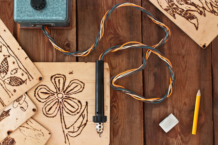 Pyrography workshop. A pyrography tool and a floral model. Standard-Bild