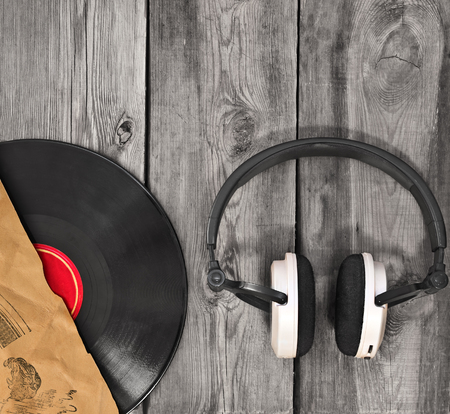 Vinyl  record, paper cover and headphones on on the old wooden background