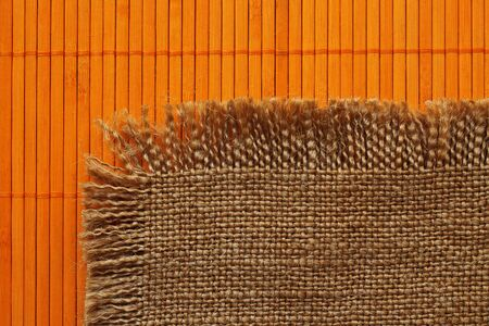 Old grunge retro backing of burlap on the orange bamboo  mat