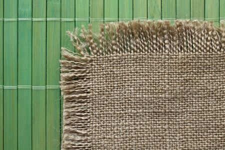 woven: Old grunge  backing of burlap on the green bamboo  mat