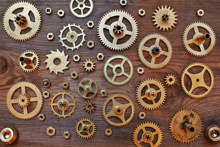 Mechanical cogs gears wheels on wooden background Stock Photo